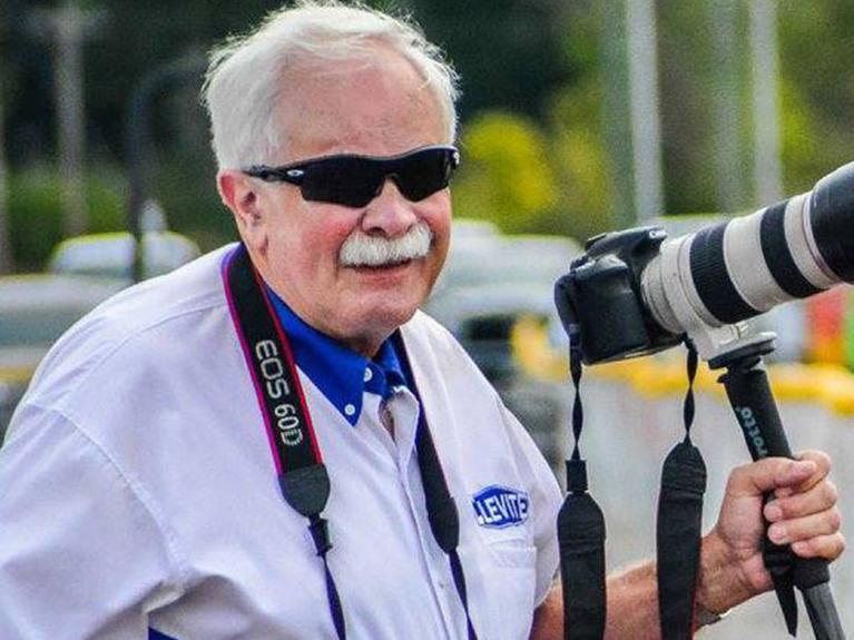 Bill McKnight in MAHLE Clevite logo shirt and professional DSLR camera on the side of the drag strip