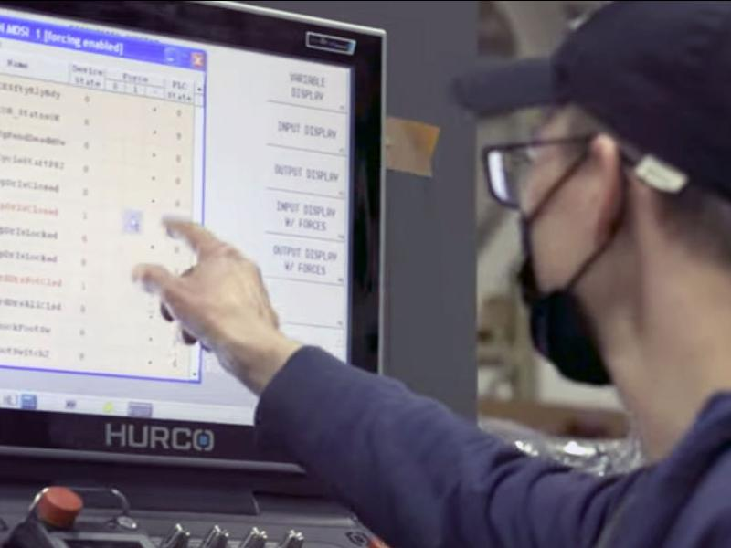Two industry professionals working on a Hurco machine